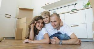 El padre y la madre hermosos juegan y abrazan a su pequeño hijo mientras que miente en el piso familia que se relaja y que ríe de
