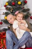El padre y la pequeña hija debajo de un árbol del Año Nuevo Imagen de archivo