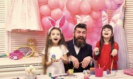 El padre y las hijas est?n pintando los huevos fotos de archivo libres de regalías