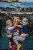 El padre y los niños permanecen cerca de la orilla de mar en Garachico Imagen de archivo