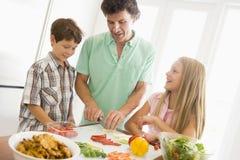 El padre y los niños preparan la comida de A Foto de archivo libre de regalías