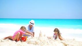 El padre y los niños que hacen la arena se escudan en la playa tropical metrajes