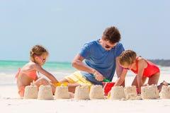 El padre y los niños que hacen la arena se escudan en la playa tropical Fotos de archivo