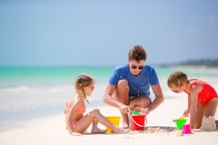 El padre y los niños que hacen la arena se escudan en la playa tropical Familia que juega con los juguetes de la playa Foto de archivo