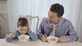 El padre y el pequeño hijo comen los copos de maíz almacen de video