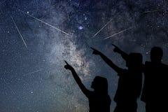 El padre y su hija están mirando la lluvia de meteoritos Cielo nocturno Imagenes de archivo