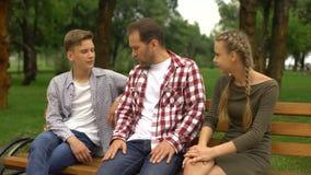 El padre y sus niños adolescentes del varón y femeninos que hablan en banco en parque, se relajan almacen de video