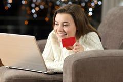 El pagar adolescente en línea con la tarjeta de crédito en casa Foto de archivo libre de regalías