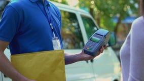 El pagar femenino la entrega del paquete vía el pago sin contacto del uso del smartphone almacen de metraje de vídeo
