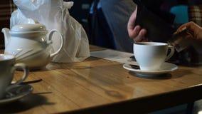 El pagar por la tarjeta de crédito en café El camarero con terminal toma una tarjeta sin contacto 4k almacen de video
