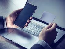 El pago en línea, ` s del hombre da sostener una tarjeta de crédito y usar el teléfono elegante para las compras en línea Imagenes de archivo
