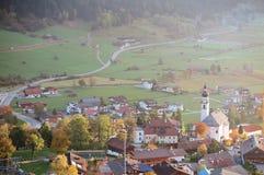 El paisaje colorido del otoño del pueblo de Lermoos se encendió para arriba por la luz de oro del sol en la madrugada imagen de archivo