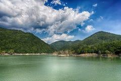 El paisaje del lago con las montañas y los árboles verdes debajo de un cielo azul con las nubes Imagenes de archivo