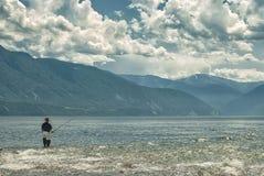 El paisaje del lago y de la nube, el pescador coge un pescado en la caña de pescar Imágenes de archivo libres de regalías