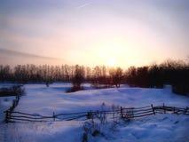 El paisaje del pueblo del prado en invierno en la puesta del sol Imagen de archivo