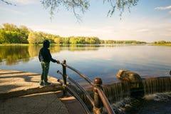 El paisaje hermoso de la primavera, un adolescente se coloca en la orilla de un lago Foto de archivo