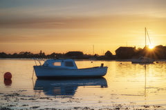 El paisaje hermoso de la puesta del sol del verano sobre puerto de la marea baja con amarra Imagenes de archivo