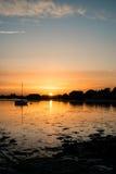 El paisaje hermoso de la puesta del sol del verano sobre puerto de la marea baja con amarra Fotos de archivo