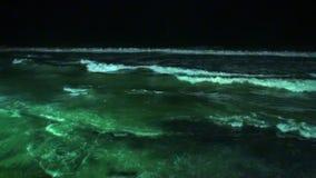 El paisaje marino y las ondas brillan intensamente en la noche en Maldivas