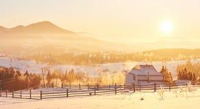 El paisaje misterioso del invierno es montañas majestuosas en invierno Puesta del sol fantástica Casas de la grabación en la niev imagenes de archivo