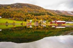 El paisaje rural del otoño con las casas acerca al río, Noruega Imagenes de archivo