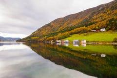 El paisaje rural del otoño con las casas acerca al río, Noruega Foto de archivo