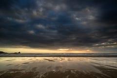 El paisaje tempestuoso dramático del cielo reflejó en agua de la marea baja en rho Fotos de archivo
