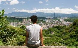 El paisaje urbano hermoso con un hombre sienta y mira lejos a Foto de archivo