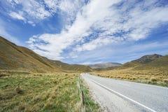 El paisaje y el camino concreto de Lindis pasan con el cielo azul brillante imagen de archivo