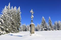El paisaje y la nieve del invierno envolvieron los árboles, cruz de piedra Imágenes de archivo libres de regalías