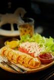 El palillo del perrito caliente de la galleta fijó con la ensalada y el té caliente en la tabla Imagen de archivo libre de regalías