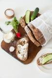 El pan con la sal, la mantequilla, el pepino y los rábanos mienten en un tablero de madera del corte en un fondo blanco Fotos de archivo libres de regalías