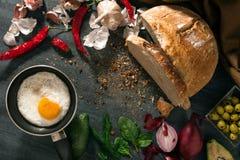 El pan de pan amargo está en la tabla Las verduras se arreglan alrededor Huevo frito en una cacerola Imagenes de archivo