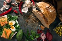 El pan de pan amargo está en la tabla Las verduras se arreglan alrededor Mentira de los huevos y de los salmones en los bocadillo Imagen de archivo