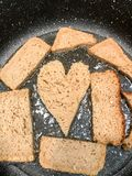 El pan de Rye se fríe en un sartén en el aceite, cuscurrones, suhariki bajo la forma de corazón imagenes de archivo
