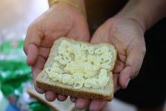 El pan del trigo integral remató con mayonesa en manos imagen de archivo libre de regalías