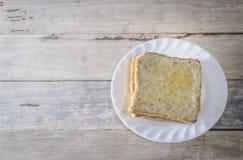 El pan en el plato blanco puso el escritorio de madera Foto de archivo