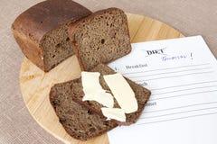El pan en tabla de cortar con mantequilla y la dieta planean Foto de archivo