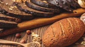 El pan entero del multigrain del grano, entero y cortado, contiene las semillas aisladas en negro almacen de video