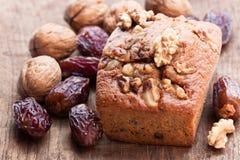El pan hecho en casa de la fecha y de la nuez se apelmaza en la tabla de madera vieja Imagen de archivo