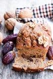El pan hecho en casa de la fecha y de la nuez se apelmaza en la tabla de madera vieja Fotos de archivo libres de regalías