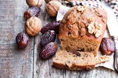 El pan hecho en casa de la fecha y de la nuez se apelmaza en la tabla de madera vieja Foto de archivo libre de regalías