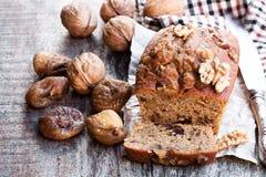 El pan hecho en casa del higo y de la nuez se apelmaza en la tabla de madera vieja Foto de archivo libre de regalías