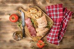 El pan italiano del ciabatta cortó en rebanadas con el salami Fotos de archivo
