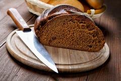 El pan negro del corte en una tabla Foto de archivo libre de regalías