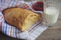 El pan recientemente cocido sirvió con el atasco y el vidrio de leche Fotografía de archivo libre de regalías