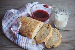 El pan recientemente cocido sirvió con el atasco y el vidrio de leche Foto de archivo libre de regalías