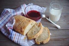 El pan recientemente cocido sirvió con el atasco y el vidrio de leche Imagen de archivo