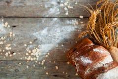 El pan y el trigo rústicos en un viejo vintage planked la etiqueta rústica de madera Foto de archivo