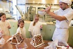 El panadero agita azúcar en polvo sobre casa de pan de jengibre